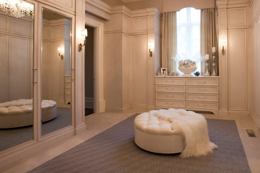 Ambient light from the wall sconces and a crystal chandelier reflected in the mirrored doors creates a warm and romantic vibe in this walk-in closet with a white dresser and a round tufted ottoman that's topped with a faux fur throw.