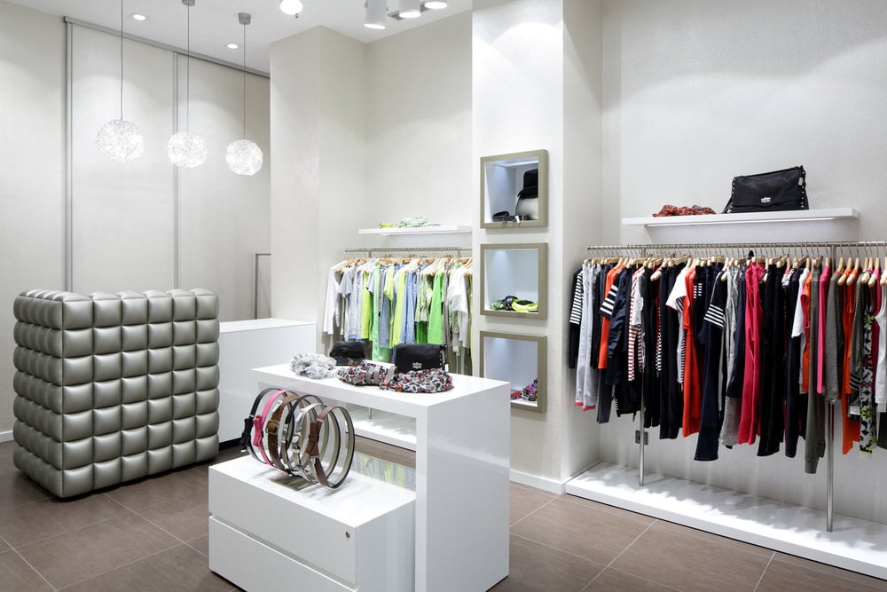 Sleek walk-in closet with wardrobe pole system and floating shelves flanking a white pillar that's mounted with a series of mirrors. It is accompanied by a two-tier island for storing accessories along with a counter under round pendants wrapped in a gray tufted cushion.