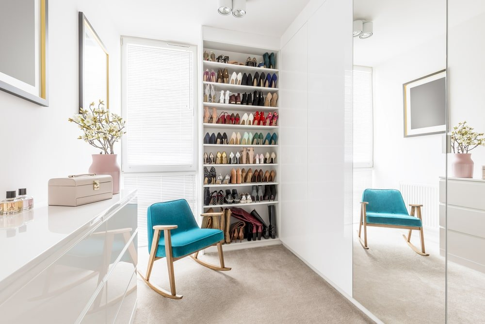 A blue cushioned rocking chair stands out in this white walk-in closet with gray carpet flooring and a full-height window that allows natural light in.