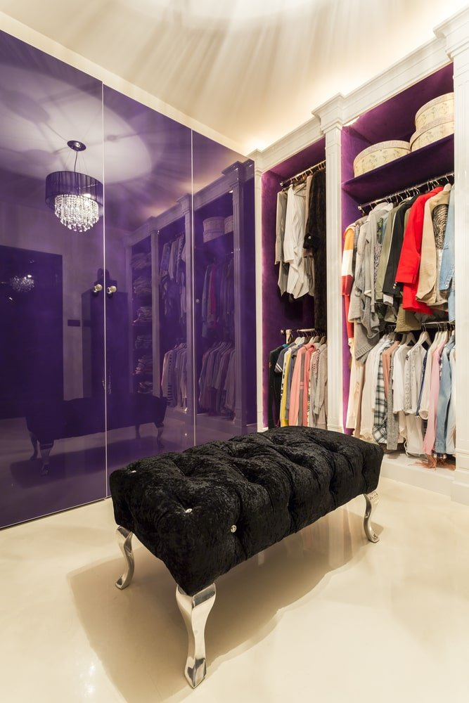 The charming walk-in wardrobe features purple mirrored doors in high gloss finish reflecting a fancy drum chandelier. It is complemented by a classy black tufted bench over beige tiled flooring.