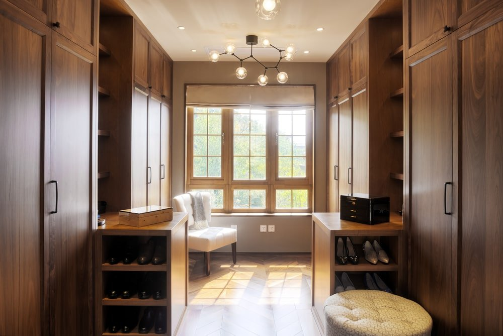 Natural light streams in through the wooden framed windows covered in beige roman shade. This walk-in wardrobe showcases cozy seats and a contemporary chandelier mounted on the tray ceiling.
