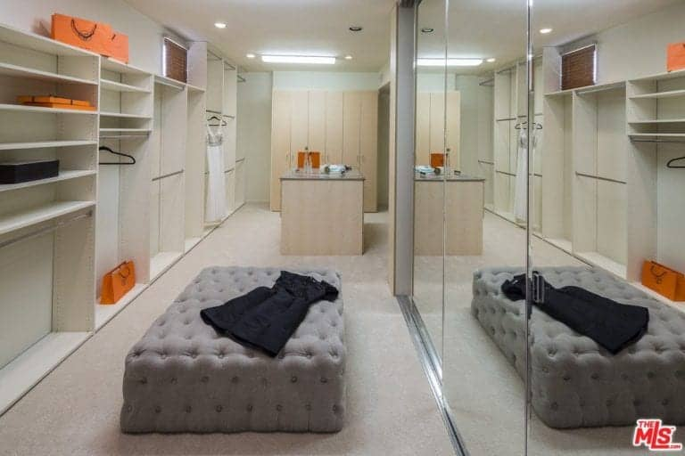 A gray tufted ottoman adds a soft touch in this sleek walk-in closet with open shelving and a light wood island that blends in with the carpet flooring. It includes mirrored wardrobe doors that create a larger visual space in the area.