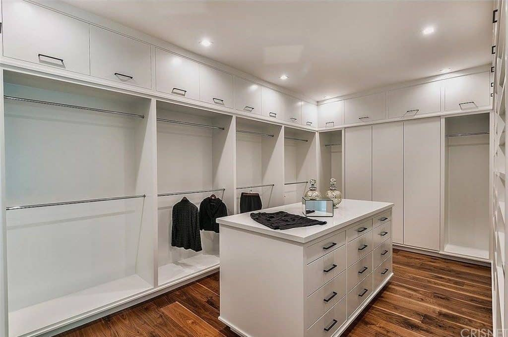 White modular cabinets surround a matching island that's accented with wrought iron pulls. This walk-in wardrobe showcases natural wide plank flooring and a regular ceiling fitted with recessed lights.