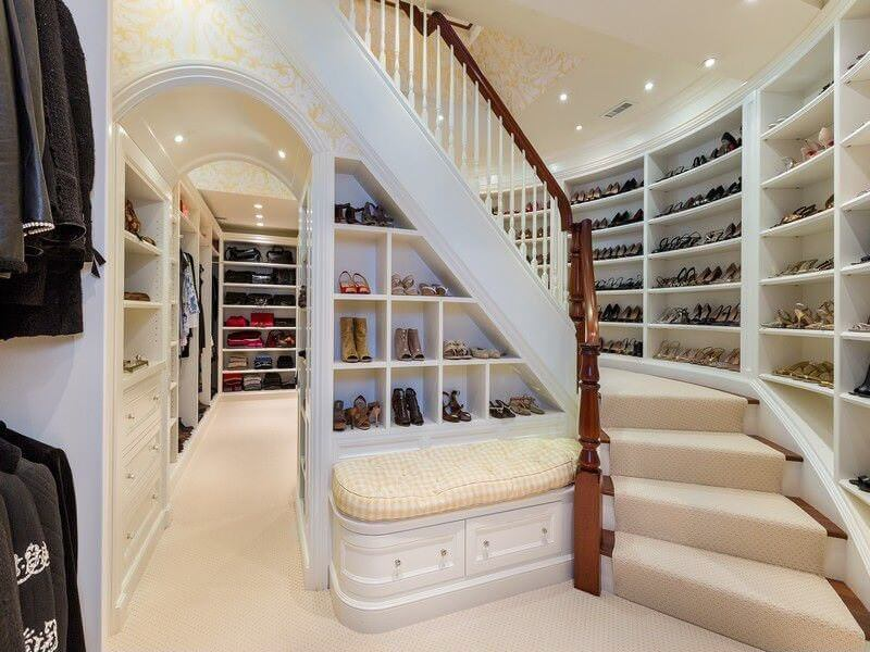 The stylish closet offers open shelving and an archway underneath the staircase that's fitted with extra storage and a seat nook. This is one great example of how you can maximize every space and niches.