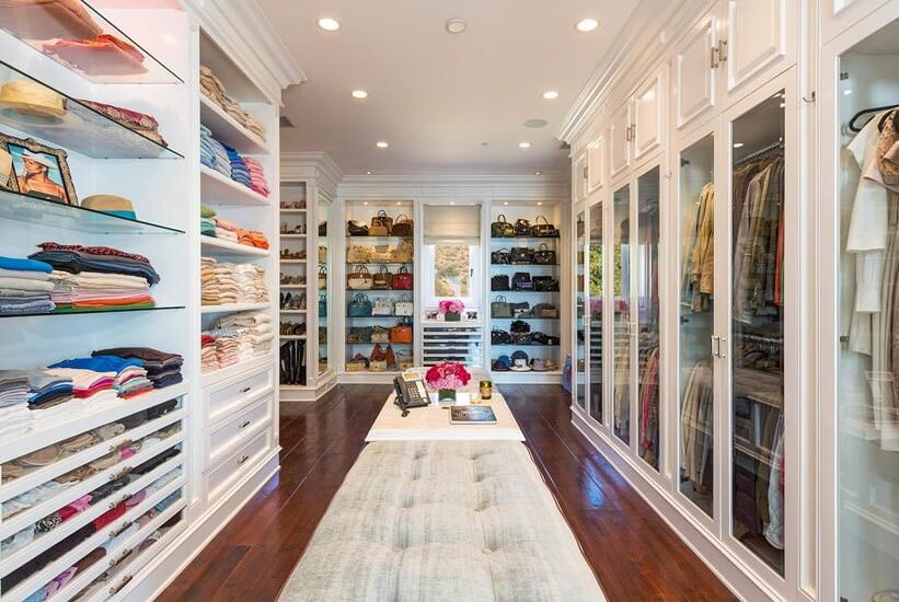 Gray tufted ottomans flanked a white table that's surrounded by open shelving and glazed wardrobe doors. This large walk-in closet has rich hardwood flooring and a regular white ceiling fitted with recessed lights.