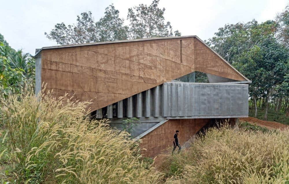 This is an exterior view of the house that is surrounded by lush landscaping of trees and shrubs that pair well with the earthy textured exteriors walls supported by unique concrete structures that has a pattern to it.