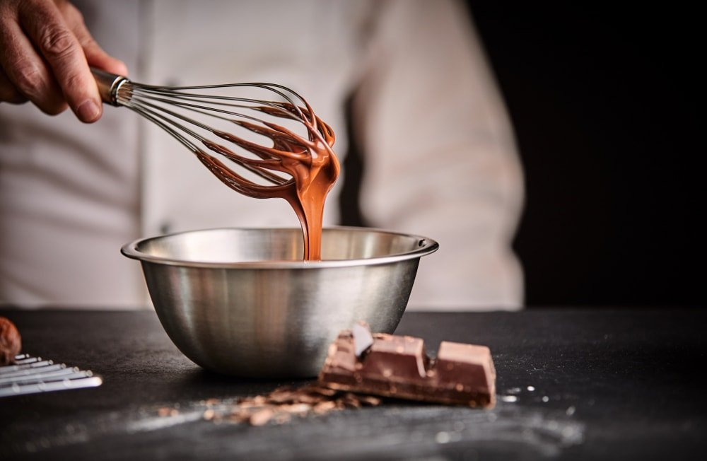 Whisking a bowl of melted chocolate.