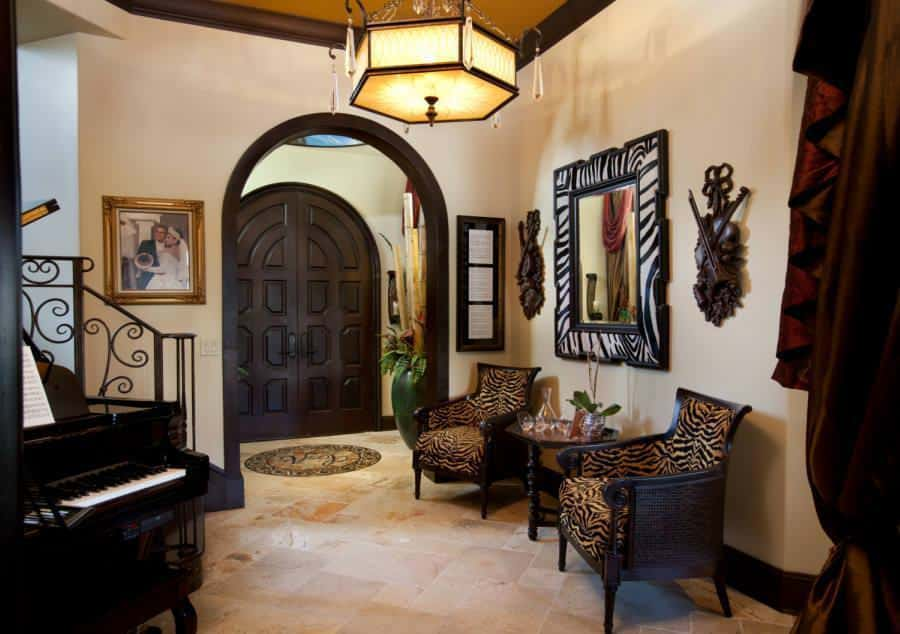 The lovely foyer has a small space but more than makes up for it with warmth. It has a grand piano on one side paired with a couple of upholstered arm chairs flanking a small side table topped with a wall-mounted mirror.