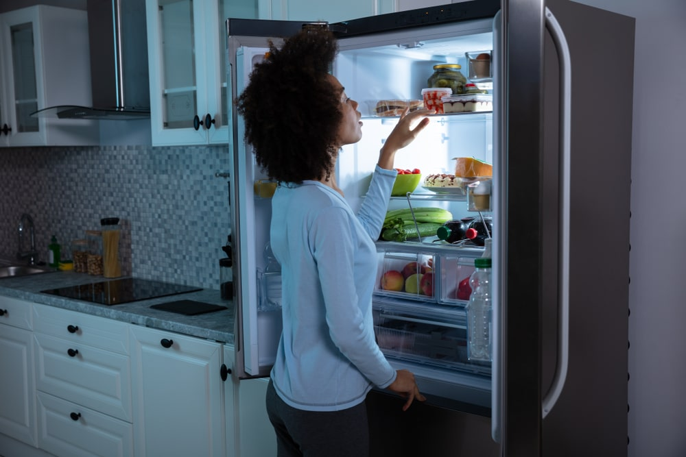 Woman searching for food in the fridge.