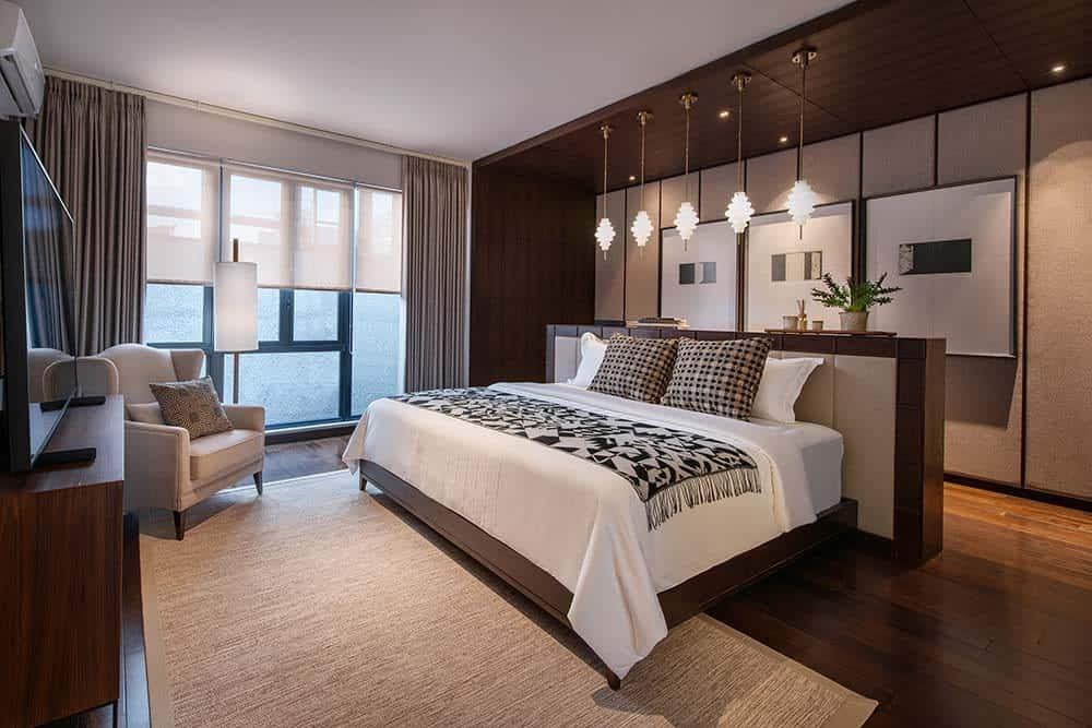 This is the primary bedroom with a large wooden platform bed with a large wooden structure at its headboard topped with decorative pendant lights hanging from wooden panels of the ceiling that matches the walls and hardwood flooring.