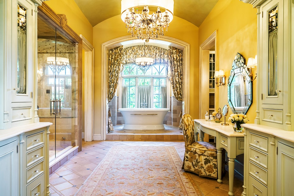 Classic primary bathroom illuminated by fancy drum chandeliers and traditional sconces mounted on the yellow wall. It has a freestanding tub and a spacious walk-in shower along with marble top vanity that's paired with a gorgeous mirror and a skirted floral chair.