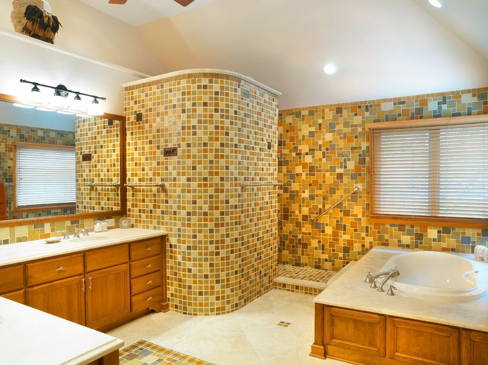 Wrought iron sconces illuminate the L-shaped vanity matching with the corner tub by the glazed window covered in roller blinds. It is accompanied by a walk-in shower that's clad in stunning mosaic tiles.