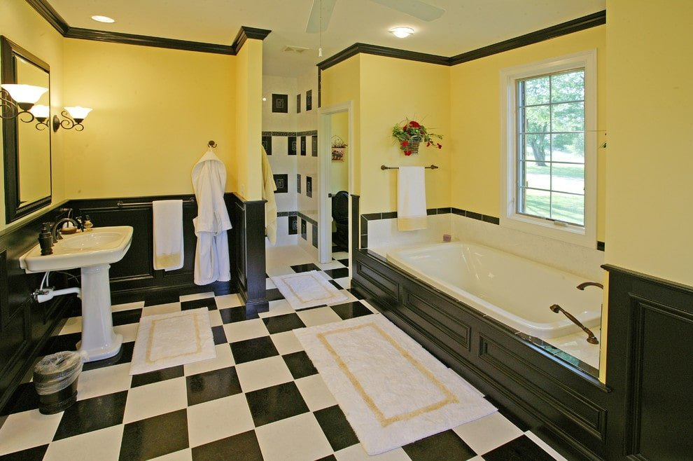 Yellow master bathroom with black wainscoting and checkered flooring topped by white bordered rugs. It includes a deep soaking tub and a pedestal sink under the framed mirror.