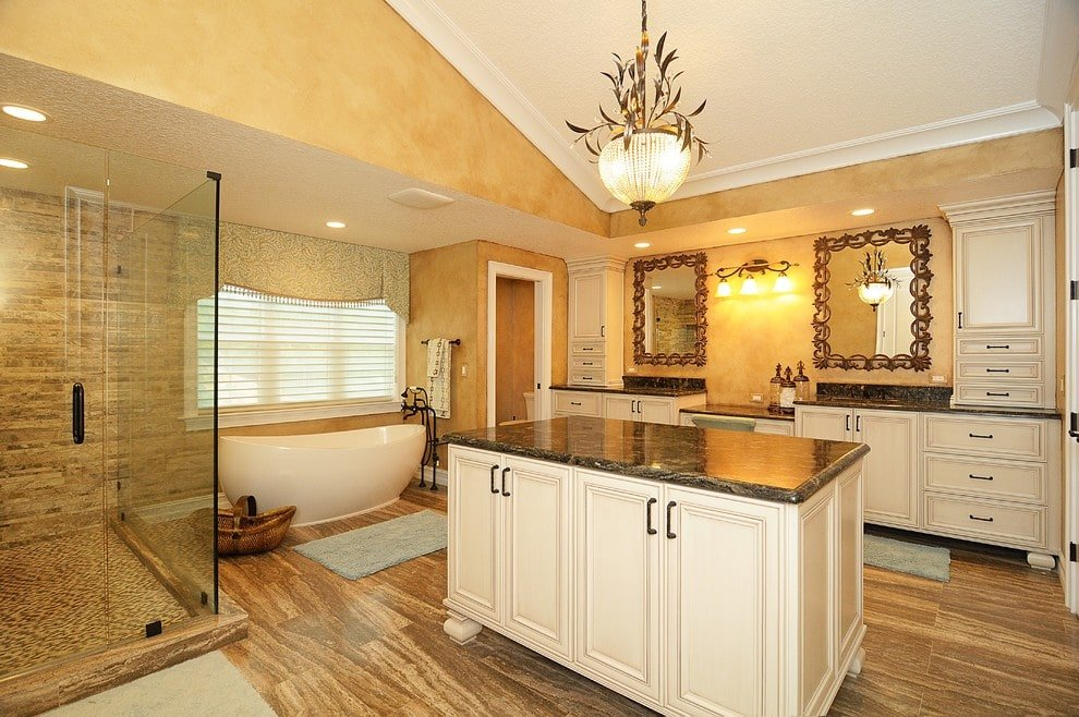 A pair of ornate mirrors hang above the white vanities matching with the granite top island that's illuminated by a gorgeous pendant. It is accompanied by a walk-in shower and a freestanding tub by the glazed window dressed in a patterned valance.