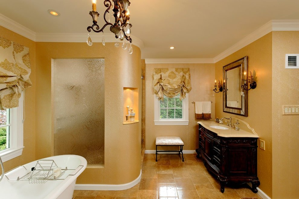 Matching sconces and a vintage chandelier illuminate this primary bathroom showcasing a freestanding tub and a cushioned stool flanked by a walk-in shower and dark wood vanity. This room has marble tile flooring and white framed windows dressed in patterned roman shades.