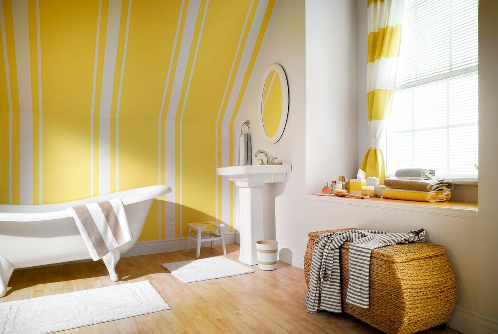 Natural light streams in through the glazed window that's covered with a yellow striped curtain. This master bathroom boasts a rattan storage and a pedestal sink facing the clawfoot tub over the light hardwood flooring topped by white rugs.