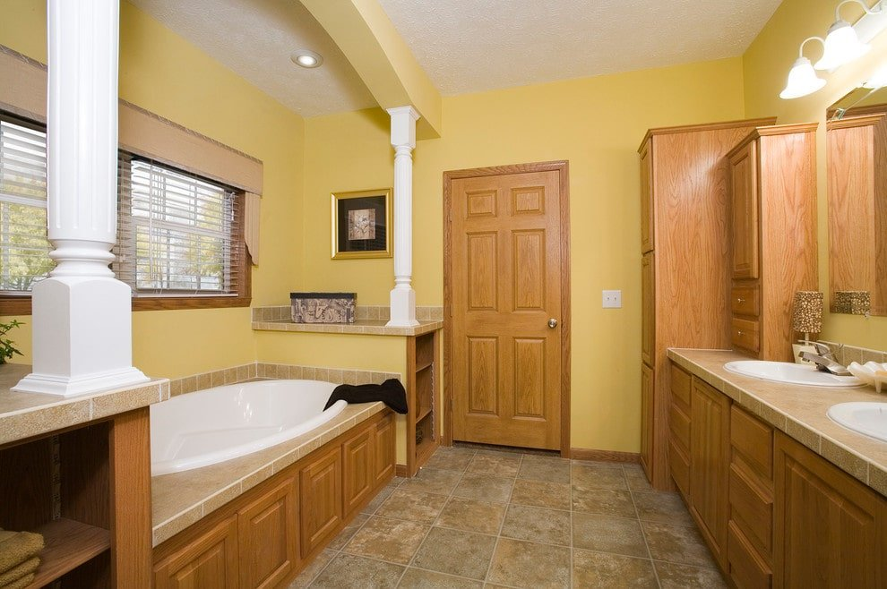 A wooden door matches the cabinets and a dual sink vanity that's fixed across the alcove tub lined with white columns. This room is decorated with a brass framed artwork and chrome sconces mounted above the frameless mirror.