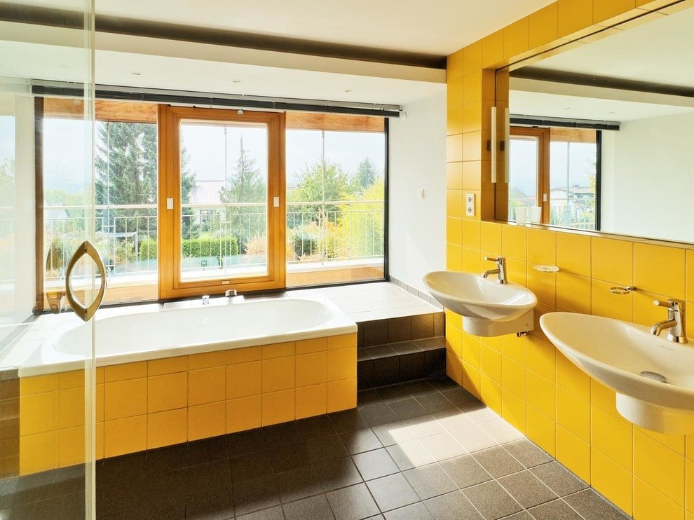 The contemporary primary bathroom boasts a deep soaking tub along with his and her wall mount sinks that are fixed against the yellow tiled wall. It has full height windows and a glazed door leading out to the balcony.