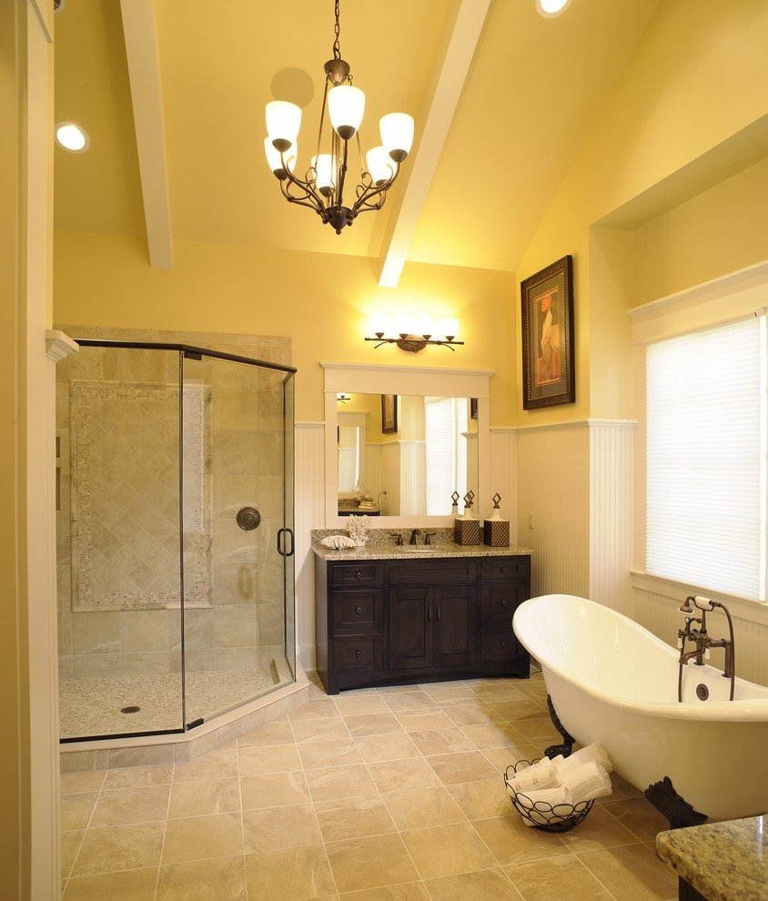 This primary bathroom is decorated with a wrought iron chandelier and an interesting artwork mounted above the beadboard lower wall. It has a clawfoot tub and a dark wood vanity next to the walk-in shower.