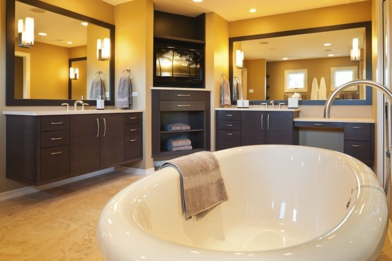 Floating vanities flank a built-in cabinet and TV facing the freestanding tub with a gooseneck faucet. It is illuminated by recessed ceiling lights and cylindrical sconces mounted on the rectangular mirrors.