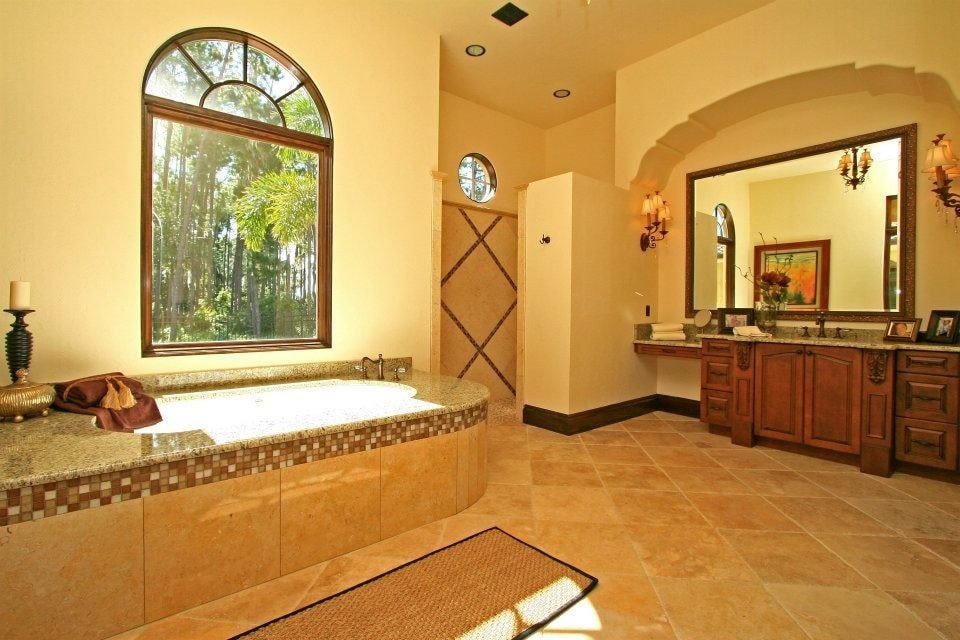 Classic sconces illuminate the wooden vanity with granite countertop and a large framed mirror. It is accompanied by a walk-in shower and a deep soaking tub by the arched window framing the outdoor greenery.