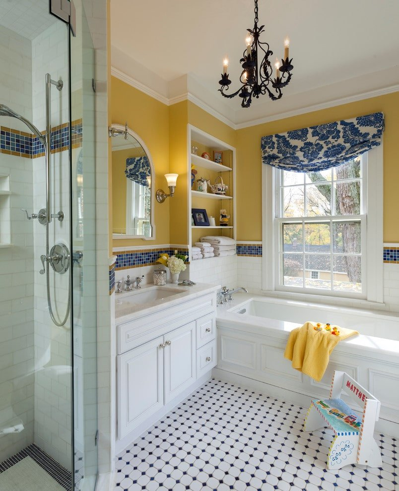 An arched mirror hangs above the sink vanity flanked by a walk-in shower and deep soaking tub under the white framed window dressed in a blue floral roman shade. It is illuminated by chrome sconces and a wrought iron chandelier.