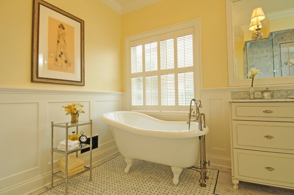 The traditional primary bathroom offers a white vanity and a clawfoot tub with a chrome shelving unit on its side. It is decorated with a lovely wall art mounted above the white wainscoting.