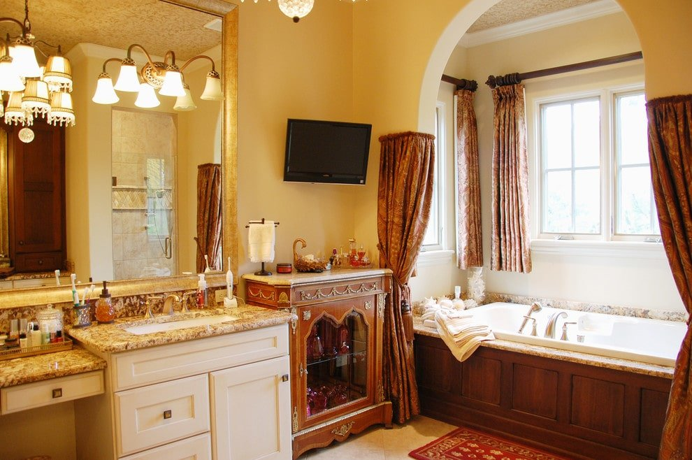 A wall mount TV hangs above the glass front cabinet that's topped with a beige granite countertop. It is flanked by a white vanity and an alcove tub dressed in classic draperies.
