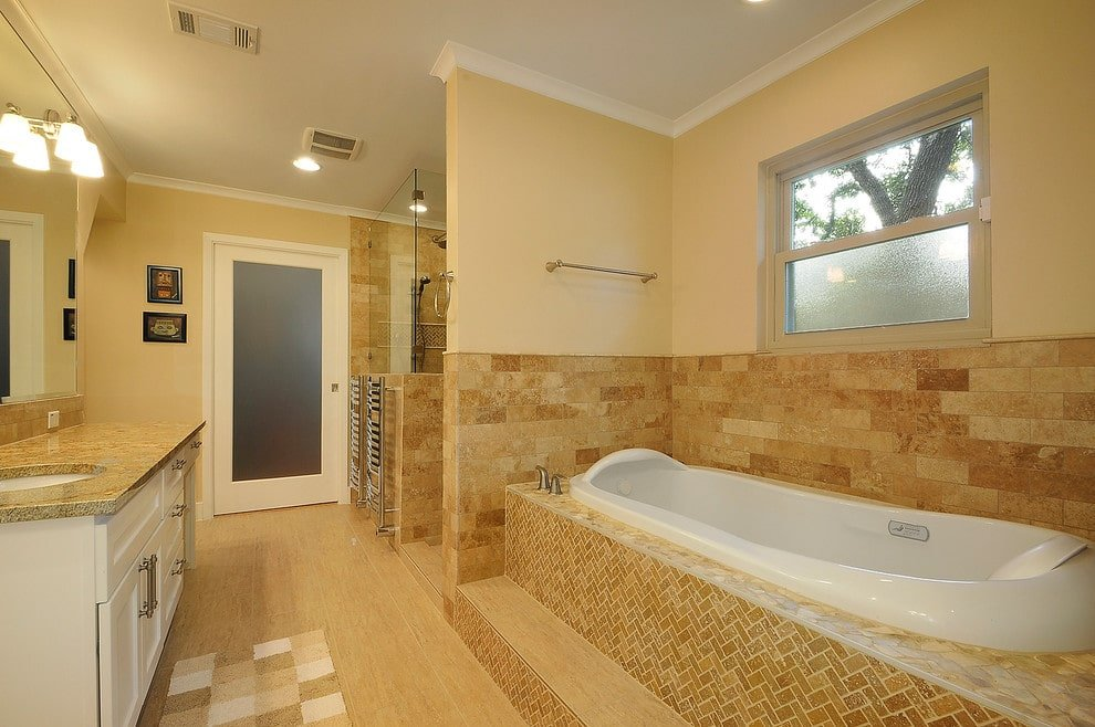 A white framed window is fixed above the brick backsplash and a deep soaking tub that's clad in beige marble tiles arranged in a herringbone pattern. It is accompanied by a walk-in shower and a white vanity with granite countertop.