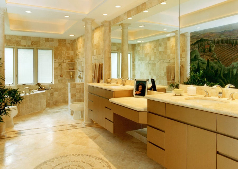 This primary bathroom is designed with a large scale mural reflected in the frameless mirror. It has his and her sink vanity along with a corner tub and toilets that are lined with marble columns.
