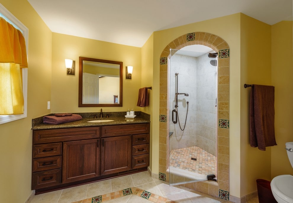Yellow primary bathroom with beige tiled flooring and a picture window dressed in a mustard curtain. It includes a toilet and a walk-in shower along with a dark wood vanity under the wooden framed mirror flanked by glass sconces.