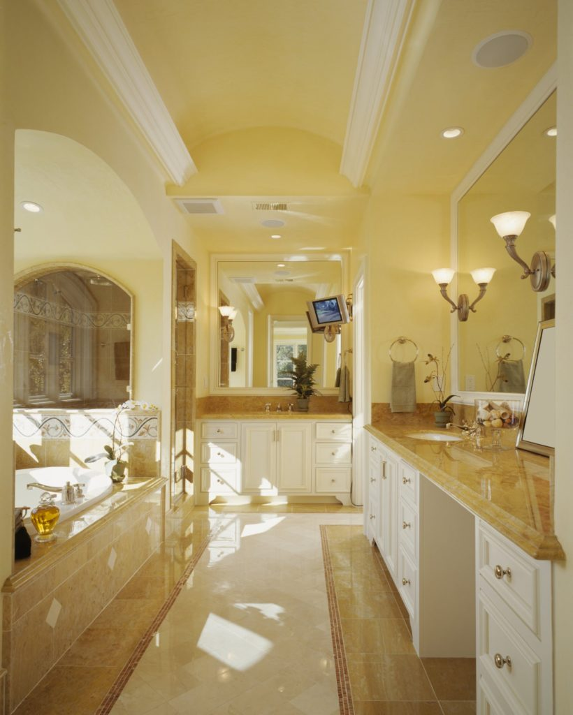 Galley master bathroom with a pair of sink vanities and an alcove tub situated next to the walk-in shower. It has beige tiled flooring and a barrel vaulted ceiling lined with white crown moldings.