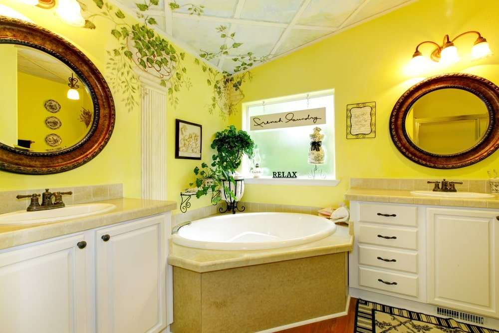 White sink vanities flank a corner tub by the picture window inviting natural light in. It is paired with round mirrors that are mounted on the yellow walls designed with plants mural.