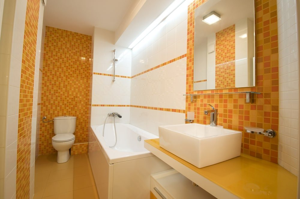 Yellow mosaic tile panels add a stunning accent in this primary bathroom showcasing a deep soaking tub and a toilet along with a vessel sink vanity under the glass floating shelf and frameless mirror.