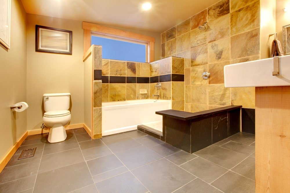 The warm master bathroom boasts a traditional toilet and an open shower area next to the deep soaking tub. It has gray tile flooring and yellow walls dominated by marble tile backsplash.