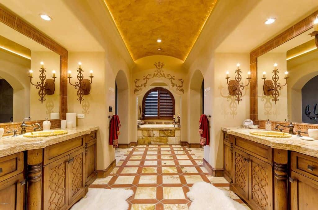 A deep soaking tub by the louvered window is the focal point in this primary bathroom with tiled flooring and a barrel vaulted ceiling mounted with recessed lights. There are arched doorways on the sides along with facing sink vanities and white faux fur rugs adding perfect symmetry in the room.