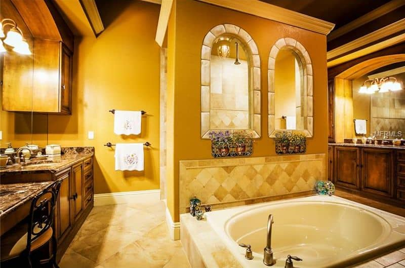 A drop-in bathtub is fixed in front of the walk-in shower with arched windows and a glass pendant light. It is surrounded by yellow walls and dark wood vanities with black granite countertops.