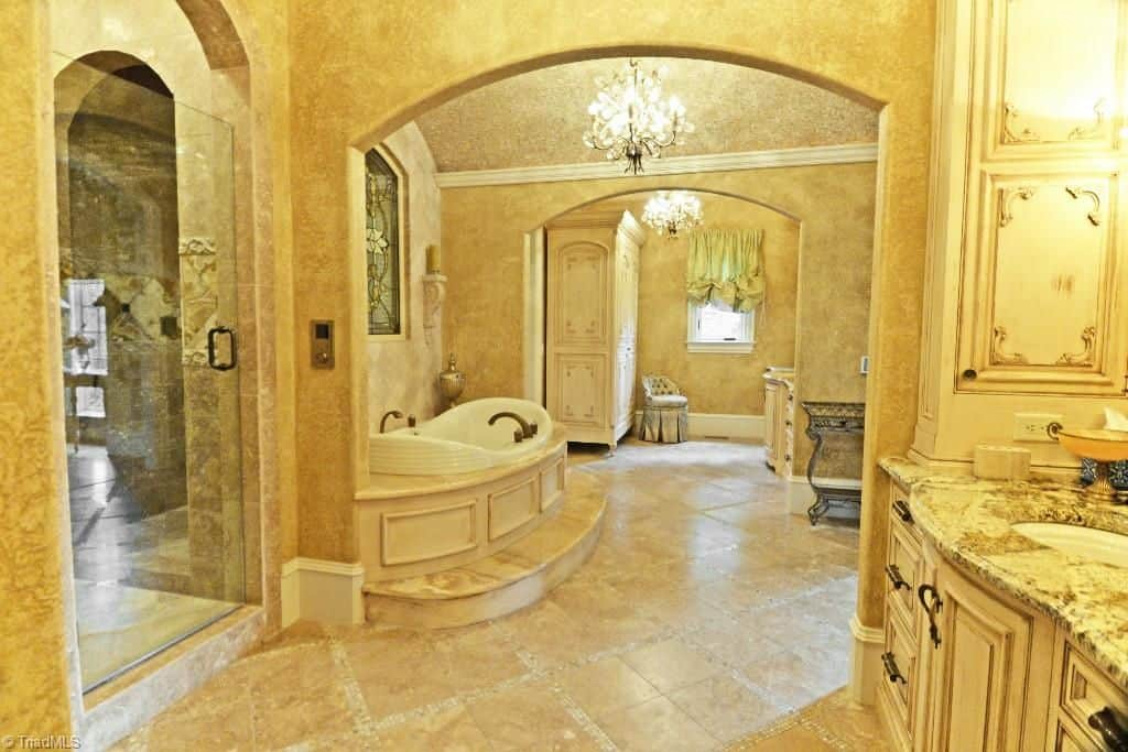 Fancy chandeliers illuminate this yellow primary bathr00m featuring a deep soaking tub by the stained glass window along with sink vanities and a full length cabinet with a skirted seat on the side.