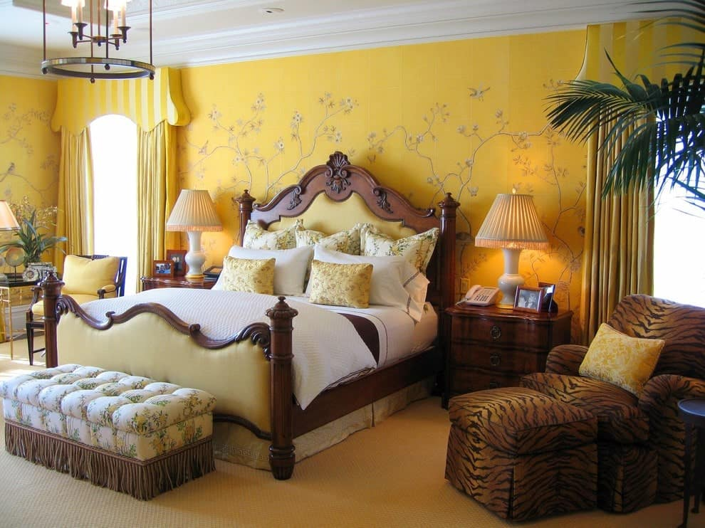 Yellow floral wallpaper sets a charming backdrop to the carved wood bed with a tufted ottoman on its end. It is accompanied by wooden nightstands and a tiger printed lounge chair accented with a yellow pillow.