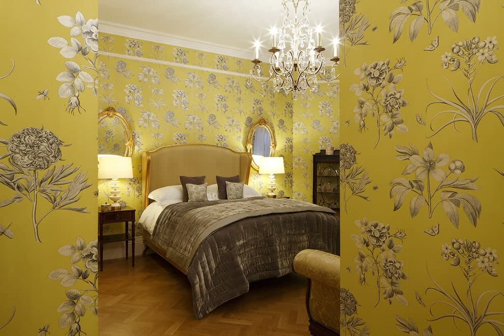 Clad in yellow floral wallpaper, this primary bedroom offers brass framed mirrors and a wingback bed over herringbone wood flooring. It is illuminated by a fabulous crystal chandelier and white table lamps that sit on dark wood nightstands.