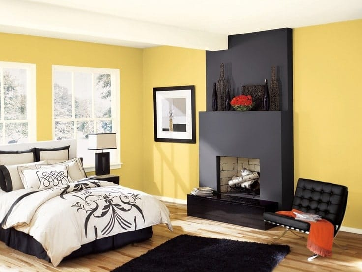 Contemporary master bedroom with a skirted bed and leather tufted chair that sits next to the sleek fireplace topped with lovely vases. It includes black framed artwork and a shaggy rug that lays on the natural hardwood flooring.
