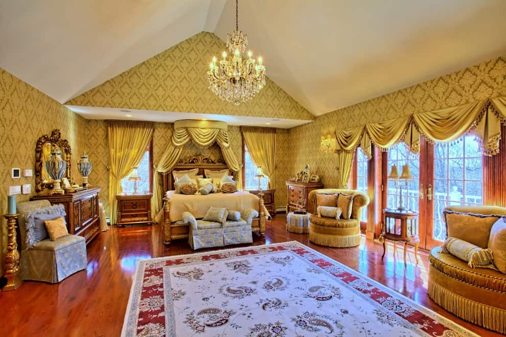 Mediterranean primary bedroom filled with elegant furniture and a classy bordered rug that lays on the rich hardwood flooring. It is illuminated by a fancy crystal chandelier that hung from the cathedral ceiling.