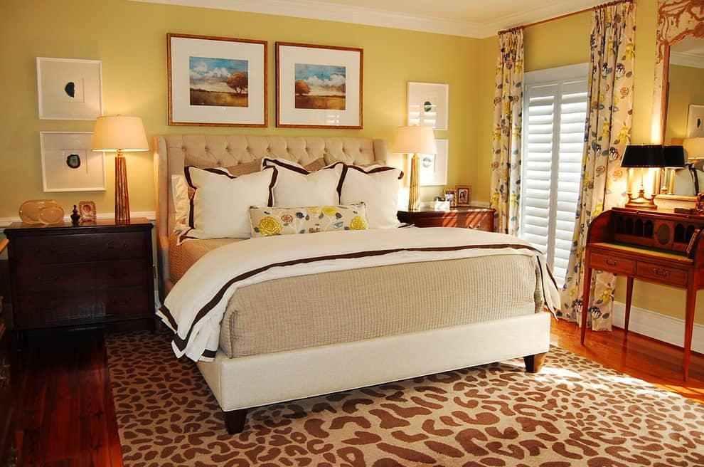 A yellow primary bedroom decorated with gallery frames that are mounted above the beige tufted bed and dark wood nightstands. It has sleek table lamps and a wooden desk that blends in with the hardwood flooring topped by a printed area rug.