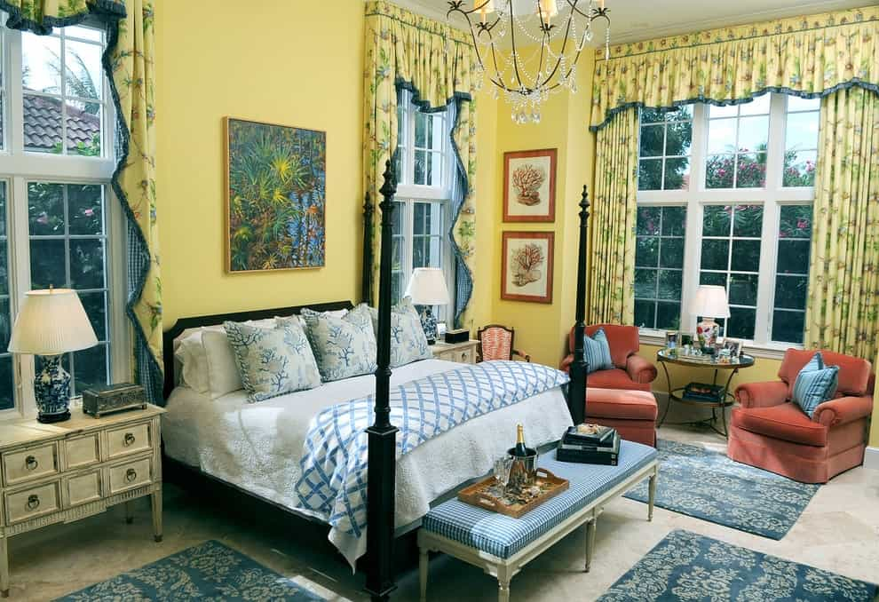 Red armchairs add a nice contrast to the yellow walls and draperies covering the full height windows. This primary bedroom features a four-poster bed in between distressed white nightstands along with blue floral rugs that lay on the gray carpet flooring.