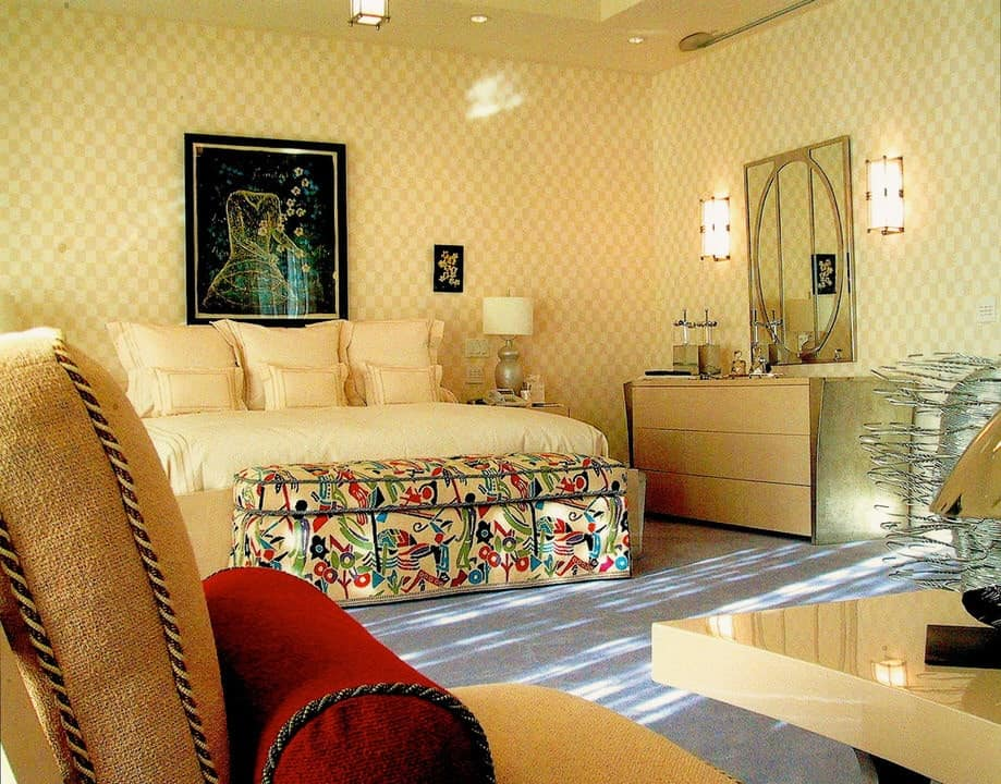 Yellow checkered wallpaper creates character in this master bedroom showcasing a light wood dresser and a comfy bed with a colorful printed ottoman on its end. It is decorated with interesting artworks and a stylish mirror flanked by glass sconces.