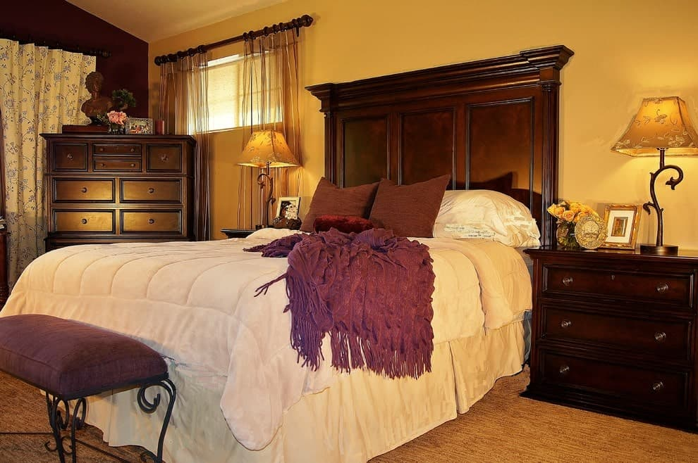 Ambient light from the charming table lamps creates a warm and cozy feel in this master bedroom with dark wood nightstands and bed matching with the dresser over the carpet flooring.