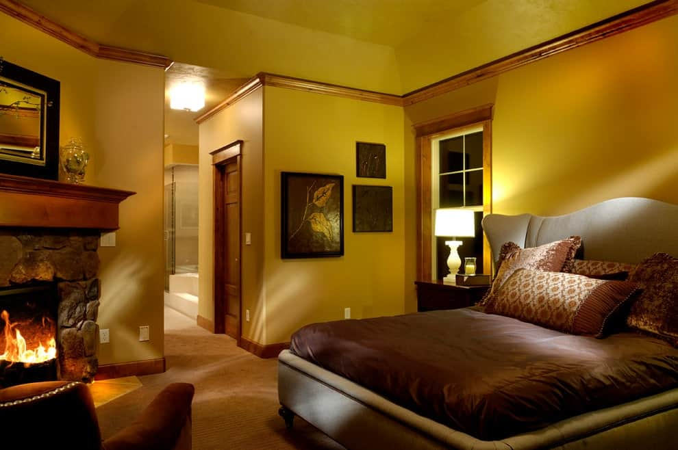 The warm master bedroom boasts a cozy chair and beige wingback bed lighted by a white table lamp. It is decorated with gorgeous wall arts and a framed mirror that hung above the brick fireplace.