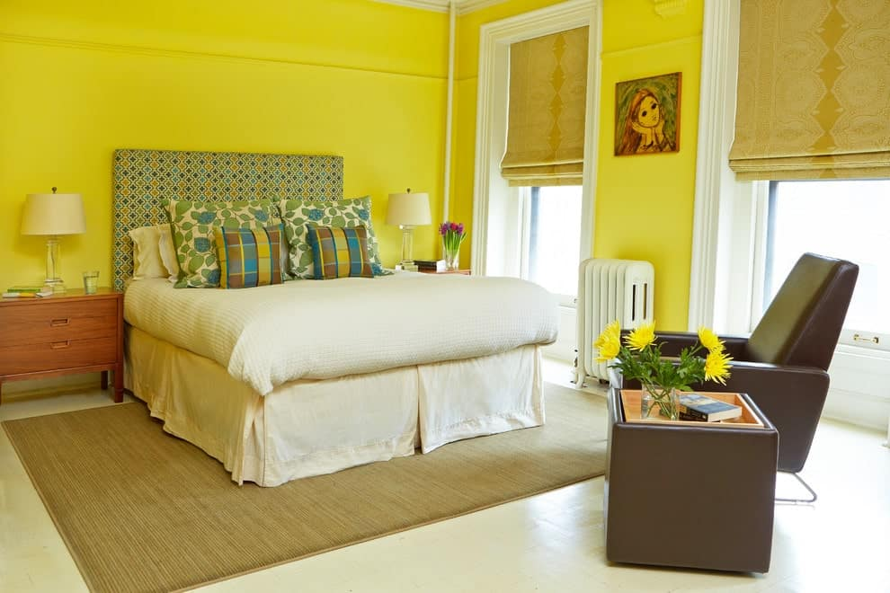 Bright yellow walls create a cheerful tone in this primary bedroom with a leather armchair and a skirted bed accented with a multi-color patterned headboard. It includes glass table lamps and a tan area rug that lays on the white tiled flooring.