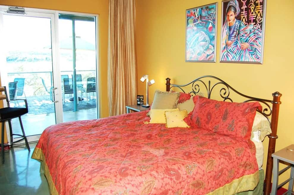 The traditional master bedroom features gorgeous paintings and a metal bed that's wrapped in a red blanket adding a striking contrast to the yellow walls. It has concrete flooring and a glass slider that opens to the porch.