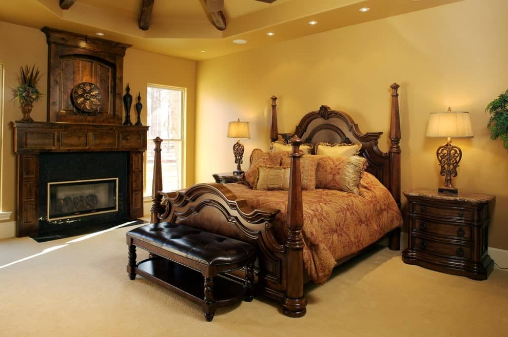A leather tufted bench sits in front of the four-poster bed flanked by matching nightstands and stylish table lamps. There's a fireplace on the side that's framed with a wooden mantel.